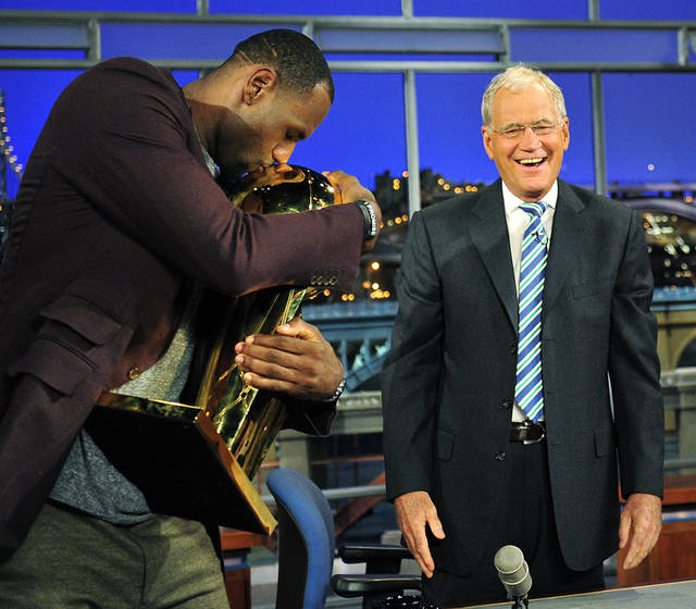 "In this photo provided by CBS, Miami Heat's LeBron James, left, embraces the Larry O'Brien trophy as television show host David Letterman watches, Tuesday, June 26, 2012, on the set of the ""Late Show with David Letterman"" in New York. James and the Miami Heat defeated the Oklahoma City Thunder to claim the 2012 NBA Championship. (AP Photo/CBS, John Paul Filo) MANDATORY CREDIT; NO ARCHIVE; NO SALES; NORTH AMERICA USE ONLY"