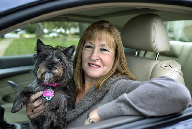 This Nov. 2, 2012 file photo shows Diane Spitaliere and her pet dog Izzie sitting in her car outside her house in Alexandria, Va. Women have passed men on the nation�s roads. More women now have driver�s licenses than men, a reversal of a longtime gender gap behind the wheel that transportation researchers say is likely to have significant safety and economic implications. Spitaliere, 58, a retired government worker says: �I want to be in my own car for as long as possible. I want to be independent for as long as I can.� (AP Photo/Manuel Balce Ceneta, File)