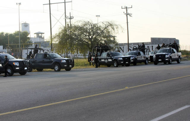 A group of Mexican federal police stand in front of the prison in Piedras Negras, Mexico, Monday Sept. 17, 2012. Authorities say 132 inmates have escaped from this jail in northern Mexico, sparking a search by federal police and soldiers in an area close to the U.S. border. (AP Photo/Adriana Alvarado)