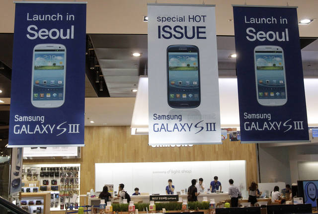 Banners advertising Samsung Electronics' Galaxy S III smartphones are displayed at a showroom in Seoul, South Korea, Friday, July 27, 2012. Samsung, the world's largest technology company by revenue, reported another record-high quarterly profit as customers flocked to Galaxy smartphones, helping it outdo rivals at a challenging time for the global tech industry. Samsung Electronics Co.'s net profit swelled to 5.2 trillion won ($4.5 billion) in the April-June quarter, a 48 percent jump from a year earlier. (AP Photo/Ahn Young-joon)