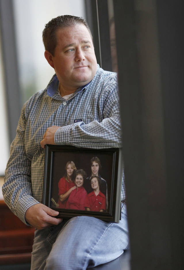 Allen Carson sits with a portrait of his family taken when he was younger. Carson's mom was diagnosed with schizophrenia, and he endured a rocky childhood because of it. Photo by Doug Hoke, The Oklahoman