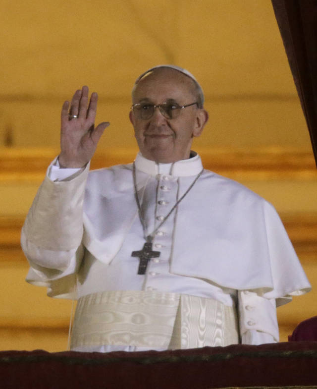 Pope Francis waves to the crowd from the central balcony of St. Peter's Basilica at the Vatican, Wednesday, March 13, 2013. Cardinal Jorge Bergoglio who chose the name of  Francis is the 266th pontiff of the Roman Catholic Church. (AP Photo/Gregorio Borgia) ORG XMIT: VAT130