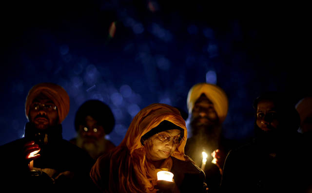 Surjit Kaur Gill, of Worcester, Mass., joins a group of Sikhs from around the Northeastern U.S., in a moment of prayer as a memorial service is broadcast over a loudspeaker outside Newtown High School for the victims of the Sandy Hook Elementary School shooting, Sunday, Dec. 16, 2012, in Newtown, Conn. (AP Photo/David Goldman) ORG XMIT: CTDG137