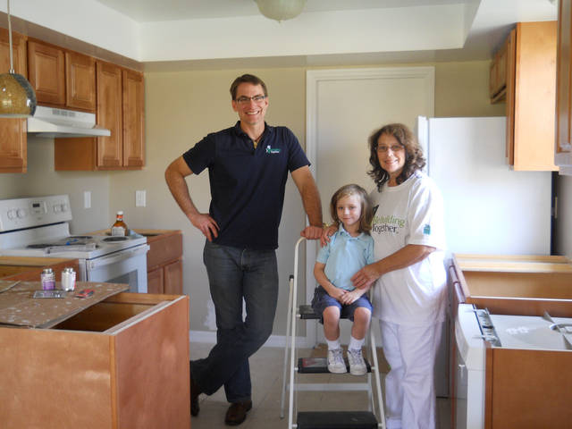 Linda Lipofsky, of Orlando, stands in her kitchen with grandson David Lipofsky, 4, and Tim Parsons of Rebuilding Together. Photo provided