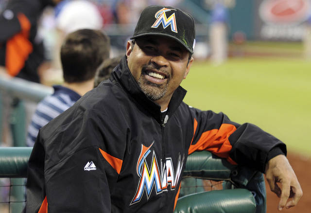 Miami Marlins manager Ozzie Guillen smiles in the dugout before a baseball game against the Philadelphia Phillies, Tuesday, Sept. 11, 2012, in Philadelphia. (AP Photo/The Express-Times, Matt Smith)