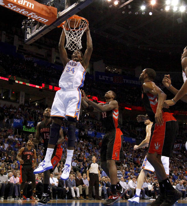 Oklahoma City's Hasheem Thabeet (34) dunks the ball beside Toronto's Ed Davis (32) during an NBA basketball game between the Oklahoma City Thunder and the Toronto Raptors at Chesapeake Energy Arena in Oklahoma City, Tuesday, Nov. 6, 2012.  Tuesday, Nov. 6, 2012. Oklahoma City won 108-88. Photo by Bryan Terry, The Oklahoman