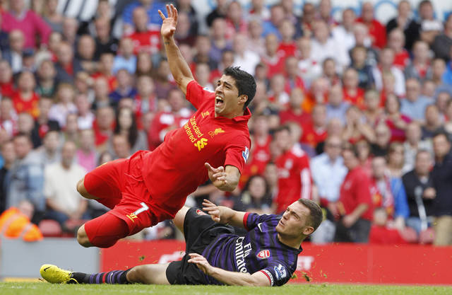 Liverpool's Luis Suarez tussles with Arsenal's Thomas Vermaelen, right, during their English Premier League match at Anfield, Liverpool England Sunday Sept. 2, 2012. Arsenal won the match 2-0. (AP Photo/ Peter Byrne/PA) UNITED KINGDOM OUT - NO SALES - NO ARCHIVES