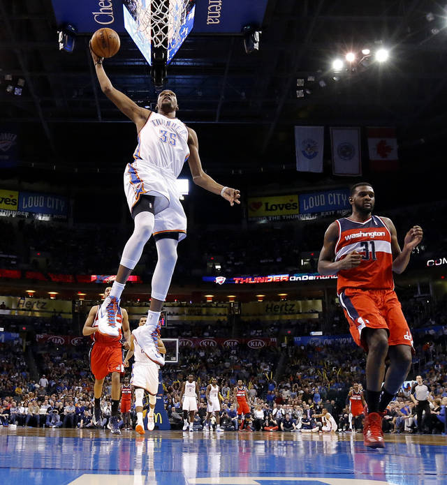 The Thunder�s Kevin Durant, left, dunks the ball beside the Wizards� Chris Singleton during Wednesday�s game at Chesapeake Energy Arena. Durant again leads the NBA in scoring. He has won the league�s scoring title three years in a row. Photo by Bryan Terry, The Oklahoman