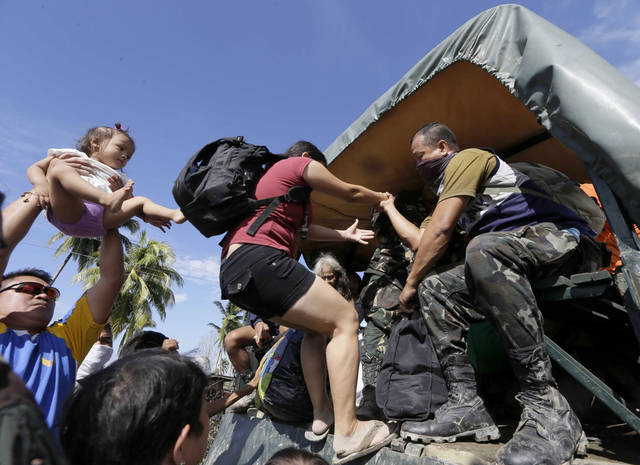 Residents are evacuated to safer grounds Thursday, Dec. 6, 2012 at New Bataan township, Compostela Valley, after Typhoon Bopha hit southern Philippines. The powerful typhoon that washed away emergency shelters, a military camp and possibly entire families in the southern Philippines has killed hundreds of people with nearly 400 missing, authorities said Thursday. (AP Photo/Bullit Marquez)