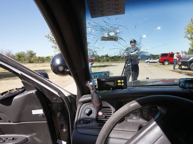 Left: A view from inside Katie Lawson's bullet-ridden police car shows what she saw the night four months ago when she was ambushed with a high-capacity rifle.  PHOTO BY PAUL HELLSTERN,  THE OKLAHOMAN ARCHIVE