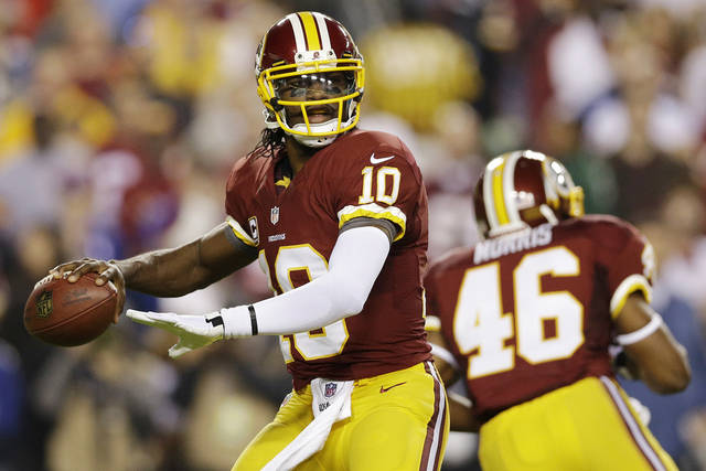 Washington Redskins quarterback Robert Griffin III looks for an open man during the first half of an NFL football game against the New York Giants in Landover, Md., Monday, Dec. 3, 2012. (AP Photo/Patrick Semansky) ORG XMIT: FDX201