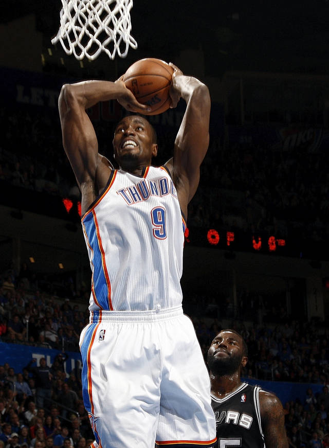 Oklahoma City's Serge Ibaka (9) dunks the ball in front of San Antonio's DeJuan Blair (45) during an NBA basketball game between the Oklahoma City Thunder and the San Antonio Spurs in Oklahoma City Monday, Dec. 17, 2012. Oklahoma City won, 107-93. Photo by Nate Billings, The Oklahoman