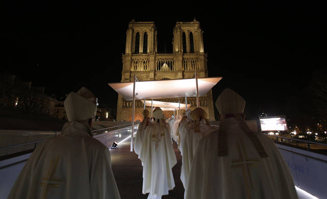 Religious dignitaries enter Paris' Notre Dame Cathedral as part of a ceremony for its 850th anniversary, Wednesday, Dec. 12, 2012. Dignitaries, tourists and Parisians gathered in the thousands for a ceremony and Mass marking the beginning of year-long commemoration of Notre Dame Cathedral's 850th anniversary. (AP Photo/Christophe Ena) ORG XMIT: ENA104