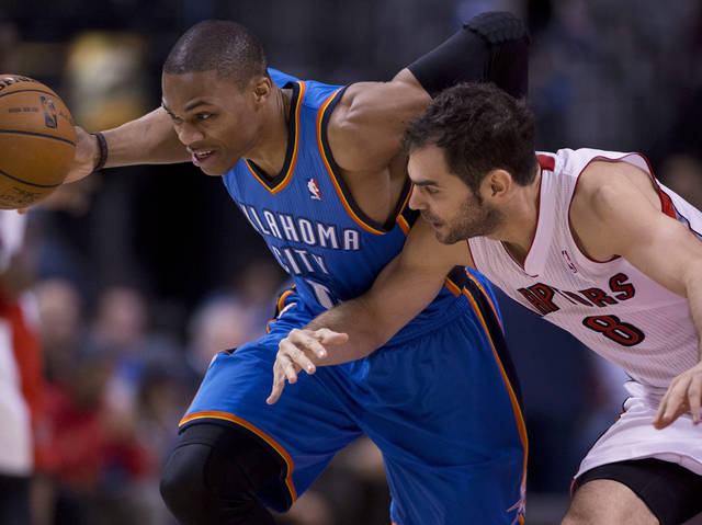 Oklahoma Thunder's Russell Westbrook, left, drives past Toronto Raptors' Jose Calderon during first-quarter NBA basketball game action in Toronto, Sunday, Jan.6, 2013. (AP Photo/The Canadian Press, Frank Gunn) ORG XMIT: FNG500