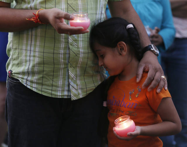 A man holds his child during a candle light vigil for the victims of the Sikh Temple of Wisconsin shooting in Milwaukee Sunday, Aug 5, 2012. An unidentified gunman killed six people at the suburban Milwaukee temple on Sunday in a rampage that left terrified congregants hiding in closets and others texting friends outside for help. The suspect was killed outside the temple in a shootout with police officers. (AP Photo/Jeffrey Phelps)