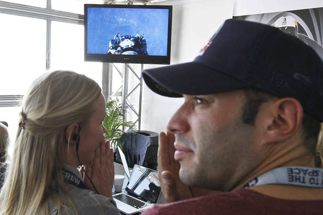 Nervous team members gather in front of a television as Felix Baumgartner, of Austria, prepares to jump from a space capsule lifted by a helium balloon at a height of just over 128,000 feet above the Earth's surface, Sunday, Oct. 14, 2012, in Roswell, N.M.(AP Photo/Ross D. Franklin) ORG XMIT: NMRF121