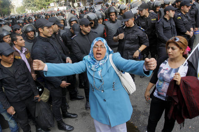 An Egyptian woman shouts anti-Mohammed Morsi slogans as soldiers block a road leading to the Shura Council where the president addressed the upper house of parliament in Cairo, Egypt, Saturday, Dec. 29, 2012. Egypt�s Islamist president warned Saturday against any unrest that could harm the drive to repair the country�s battered economy in a sharply worded speech that urged the opposition to work with his government. Mohammed Morsi made the comments in his first speech to the newly convened upper house of parliament, which he said will have full legislative powers until a new lower house of parliament is elected next year. (AP Photo/Amr Nabil)