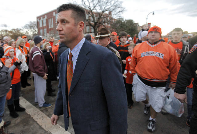 Coach Mike Gundy is followed by fans as he takes part in the 'Spirit Walk' before the Bedlam college football game between the Oklahoma State University Cowboys (OSU) and the University of Oklahoma Sooners (OU) at Boone Pickens Stadium in Stillwater, Okla., Saturday, Dec. 3, 2011. Photo by Chris Landsberger, The Oklahoman