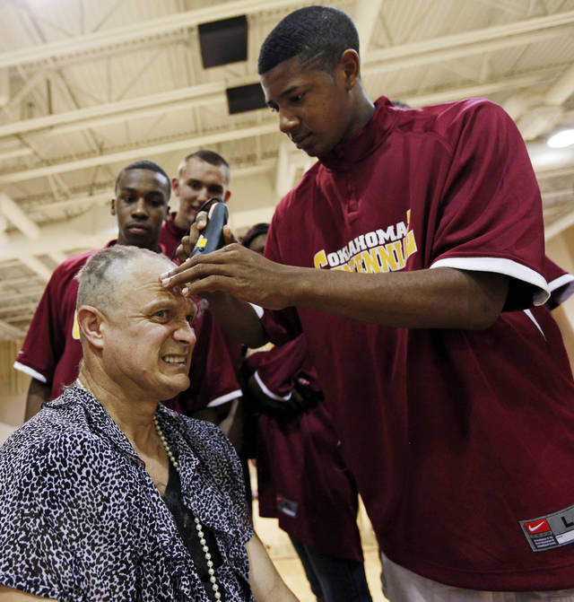 Oklahoma Centennial boys basketball coach Scott Raper wears a dress as he has his head shaved by player Keandre Wilson during an assembly to celebrate the Class 3A boys high school basketball championship by Oklahoma Centennial High School in Oklahoma City, Friday, March 30, 2012. Raper promised to have his head shaved while wearing a dress if the team won the state championship. Photo by Nate Billings, The Oklahoman