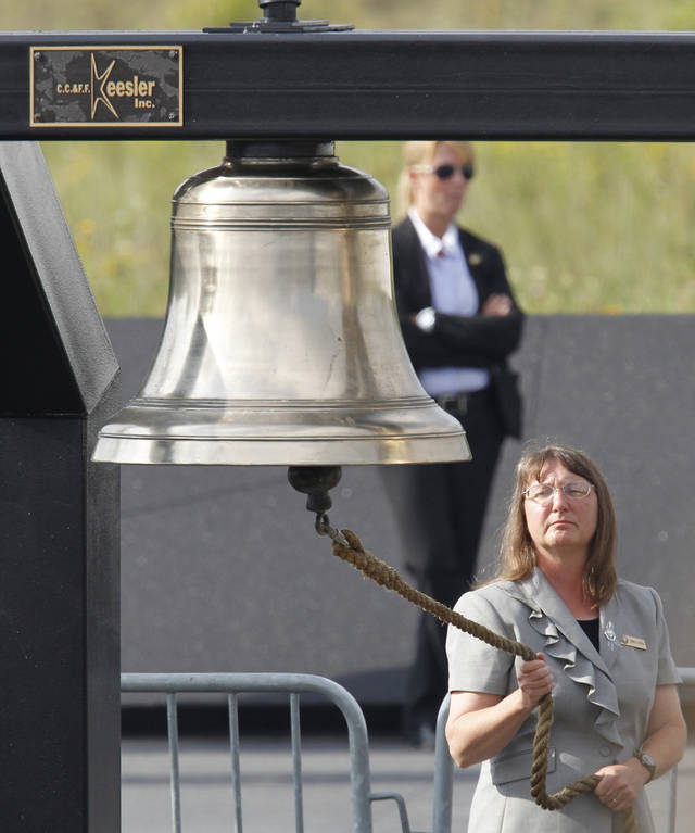 A bell is rung during the reading of the names of passengers and crew who died on Flight 93 during memorial services near the crash site of Flight 93 in Shanksville, Pa. Sunday Sept. 11, 2011.  (AP Photo/Gene J. Puskar)