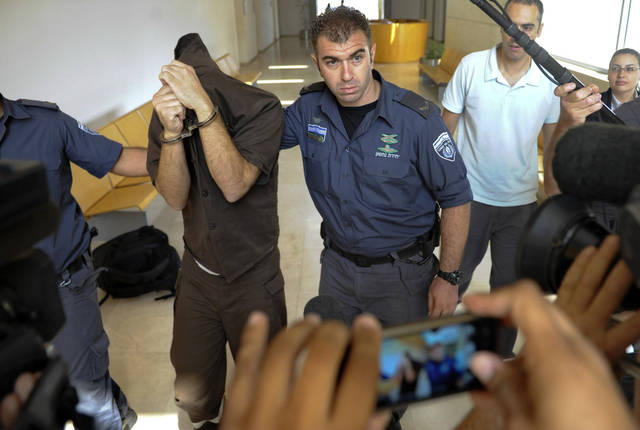 Arab citizen of Israel Milad Khatib covers his face as he is escorted at the district court in the northern Israeli city of Haifa, Thursday, Oct. 4, 2012. Israeli authorities on Thursday indicted an Arab citizen of Israel on charges of spying for the Lebanese militant group Hezbollah, accusing him of gathering intelligence on security for Israel's president and on army installations. (AP Photo/Abdullah Shama) ISRAEL OUT NOT FOR ARCHIVAL USE