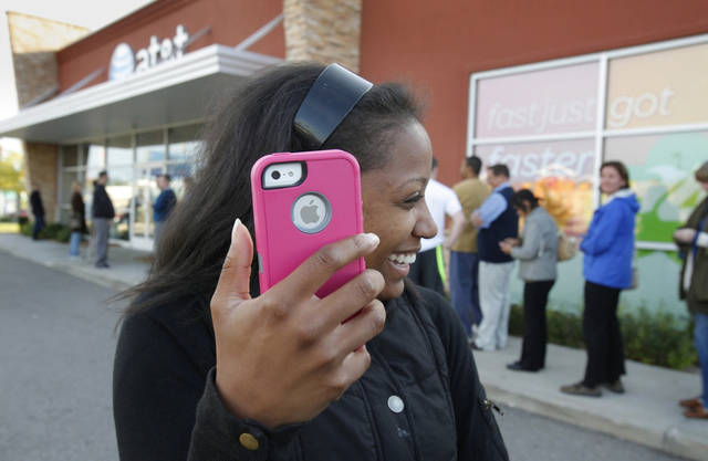 Western Michigan University student Alenna Brown ,19, leaves with her new iPhone 5 in Kalamazoo, Mich. on Friday, Sept. 21, 2012. (AP Photo/The Kalamazoo Gazette, Mark Bugnaski) ALL LOCAL TV OUT; LOCAL TV INTERNET OUT