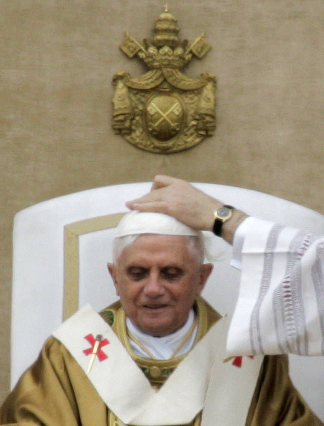 FILE - This April 24, 2005 file photo shows Vatican master of Ceremonies Archbishop Piero Marini, not pictured, adjusting the skullcap of Pope Benedict XVI during his installment Mass in St. Peter's Square at the Vatican. Pope Benedict XVI said Monday, Feb. 11, 2013 he lacks the strength to fulfill his duties and on Feb. 28 will become the first pontiff in 600 years to resign. The announcement sets the stage for a conclave in March to elect a new leader for world's 1 billion Catholics. (AP Photo/Pier Paolo Cito, files)