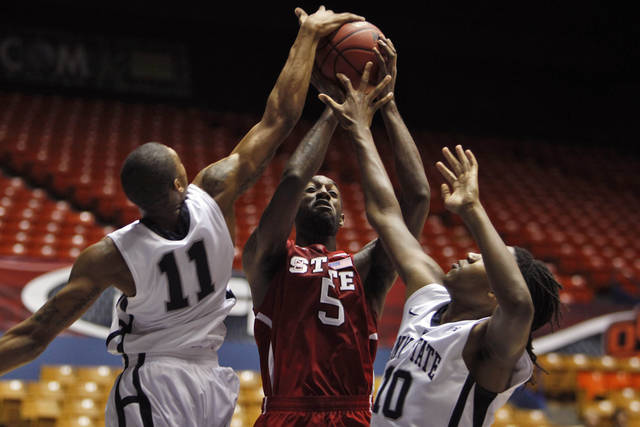 NC State's C.J. Leslie, center, goes up for a shot against Penn State's Jermaine Marshall, left, and Brandon Taylor during the first half of an NCAA college basketball game in Bayamon, Puerto Rico, Thursday, Nov. 15, 2012. (AP Photo/Ricardo Arduengo)