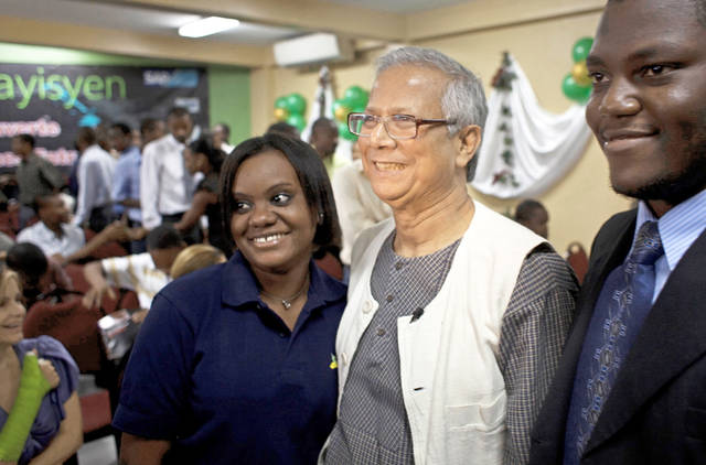 Bangladesh's Muhammad Yunus, economist and Nobel Peace Prize winner, center, gets a photo taken Friday with two students during his visit to the Etre Ayisyen technical school in Port-au-Prince, Haiti. AP photo