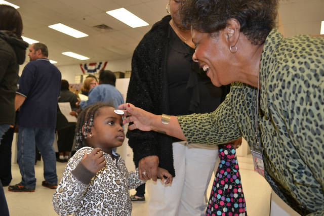 "Pat Harris, inspector for the Oklahoma County Election Board, stamps an ""I Voted"" sticker on the forehead of Kamora Beard, 3, during the second day of early voting Saturday. <strong>Zeke Campfield - The Oklahoman</strong>"