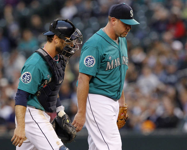 Seattle Mariners starting pitcher Kevin Millwood, right, and catcher John Jaso walk to the mound for a chat after Millwood gave up another run to the New York Yankees in the third inning of a baseball game Monday, July 23, 2012, in Seattle. (AP Photo/Elaine Thompson)