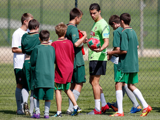 Portugal's team captain Cristiano Ronaldo signs autographs for ball boys on his way to a training session of Portugal, ahead of their Euro 2012 soccer semifinal match between Portugal and Spain slated for June 27, in Opalenica, Poland, Sunday, June 24, 2012. (AP Photo/Armando Franca)