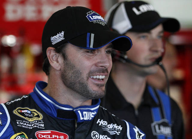 Driver Jimmie Johnson smiles as he talks with crew members in the garage before a practice for Sunday's NASCAR Sprint Cup Series AAA Texas 500 auto race at Texas Motor Speedway Friday, Nov. 2, 2012, in Fort Worth, Texas. (AP Photo/Tony Gutierrez) ORG XMIT: TMS06