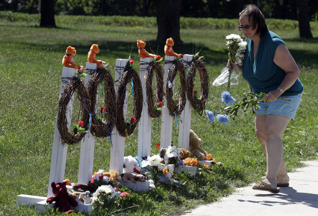 Peggy Renner-Howell lays flowers at a makeshift memorial near the Sikh Temple of Wisconsin, Tuesday, Aug. 7, 2012, in Oak Creek, Wis., where a gunman killed six people this past Sunday. A public memorial service is set for Friday for all six victims. The gunman Wade Michael Page died in an exchange of gunfire with police at the scene of the shootings. (AP Photo/M. Spencer Green)