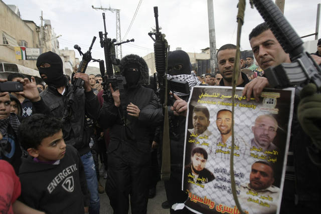 A man holds a poster showing imprisoned Palestinians as he is surrounded by armed militants in in the Balata refugee camp in the West Bank town of Nablus during a rally in support of Palestinian prisoners Friday,  Feb. 22, 2013. Israel holds a few thousand Palestinians on charges ranging from rock throwing to deadly attacks. (AP Photo/Nasser Ishtayeh)