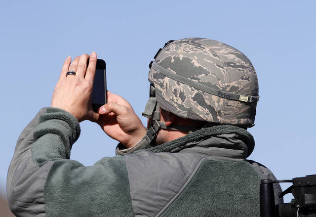 A soldier takes pictures of the parade behind him while riding in a military transport truck. The city of Midwest City teamed with civic leaders and local merchants to display their appreciation for veterans and active military forces by staging a hour-long Veteran's Day parade that stretched more than a mile and a half along three of the city's busiest streets Monday morning, Nov. 12, 2012. Hundreds of people lined the parade route, many of them waving small American flags that had ben distributed by volunteers who marched near the front of the parade. A fly-over performed by F-16s from the138th Fighter Wing, Oklahoma Air National Guard unit in Tulsa thrilled spectators. Five veterans representing military personnel who served in five wars and military actions served as  Grand Marshals for the parade. Leading the parade was the Naval Reserve seven-story American flag, carried by 100 volunteers from First National Bank of Midwest City, Advantage Bank and the Tinker Federal Credit Union. The flag is 50 feet by 76 feet, weighs 110 pounds and was sponsored by the MWC Chapter of Disabled American Veterans. Photo by Jim Beckel, The Oklahoman