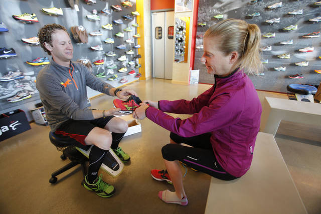 Josh Lacan shows Katie Kramer running shoes Wednesday.  Photo By Steve Gooch, The Oklahoman