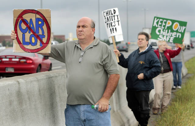 Chris Sulaitis (left), Kermyt Keaton, and Kathy Youngh join other residents of the Dove Crossing neighborhood to protest a car dealership's plans to build near them on North Interstate Drive on Saturday, May 12, 2012, in Norman, Okla.   Photo by Steve Sisney, The Oklahoman