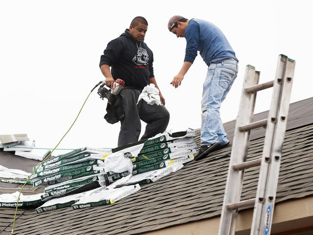 Workers install the roof of a house on SE 26 by Central Oklahoma Habitat for Humanity. Malarkey Roofing Products donated the roofing materials for 40 Habitat houses to be built this year. <strong>NATE BILLINGS - The Oklahoman</strong>