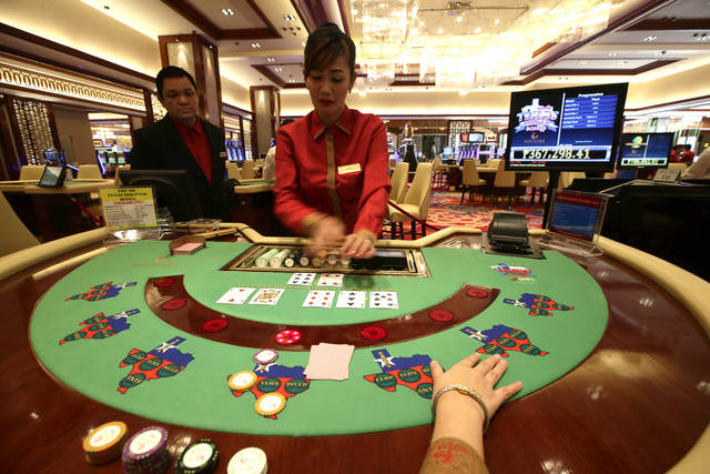 Casino dealers work on their respective games during the media tour of the new Solaire Casino, one of the country's  biggest casinos Thursday  March 14, 2013 at suburban Pasay city south of Manila, Philippines. Michael French, chief operating officer of Solaire Resort and Casino, said Thursday that studies not commissioned by his company project that the country's gaming revenue of $1.9 billion could rise to $6 billion, which is currently what Singapore generates, in about five years. Officials of a $1-billion casino resort, with majority shares owned by the country's second richest Filipino Enrique Razon Jr., say they plan to help make the Philippines one of the biggest gaming centers in the world. It is the first of four such developments on a 100-hectare (240-acre) land reclaimed from Manila Bay.(AP Photo/Bullit Marquez)