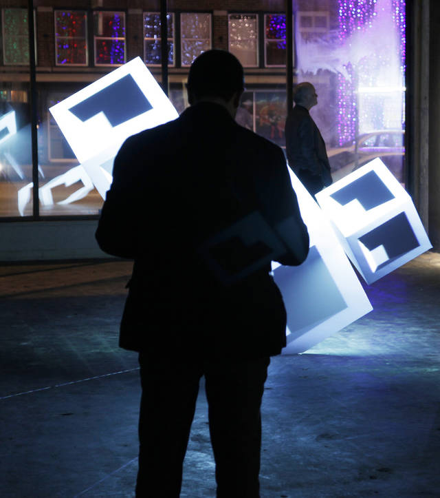 A man watches a 3D light exhibit during the opening reception for the Creativity World Art Biennale in and around Automobile Alley in Oklahoma City Wednesday, Nov. 17, 2010. Photo by Doug Hoke, The Oklahoman