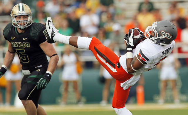 Oklahoma State's Josh Stewart (5) makes a catch as Baylor's Eddie Lackey (5) looks on during a college football game between the Oklahoma State University Cowboys (OSU) and the Baylor University Bears at Floyd Casey Stadium in Waco, Texas, Saturday, Dec. 1, 2012. Photo by Nate Billings, The Oklahoman