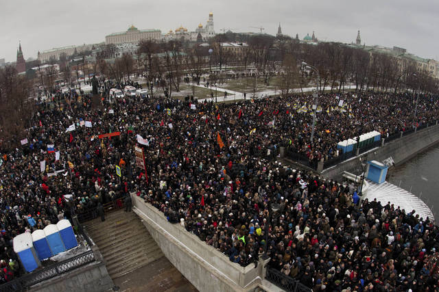 In this photo taken Saturday, Dec. 10, 2011, protesters gather to protest near the Kremlin, background, against alleged vote rigging in Russia's parliamentary elections in Moscow, Russia. Tens of thousands of people held the largest anti-government protests that post-Soviet Russia has ever seen to criticize electoral fraud and demand an end to Vladimir Putin's rule. (AP Photo/Ridus, Dmitriy Chistoprudov)