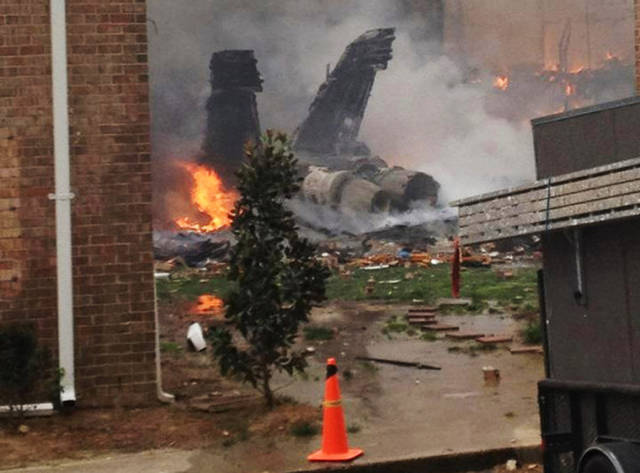 The burning fuselage of an F/A-18 Hornet lies smoldering after crashing into a residential building in Virginia Beach, Va., Friday, April 6, 2012. The Navy did not immediately return telephone messages left by The Associated Press, but media reports indicate the two aviators were able to eject from the jet before it crashed. They were being treated for injuries that were not considered life threatening. (AP Photo/Zach Zapatero)