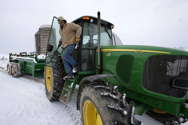 In this Saturday, Jan. 26, 2013 photo, Shawn Georgetti climbs out of his John Deere tractor on his 167-acre family dairy farm in Avella, Pa. With royalties from a Range Resources gas well on his property, Georgetti has been able to buy newer farm equipment that's bigger, faster, and more fuel-efficient. (AP Photo/Gene J. Puskar)