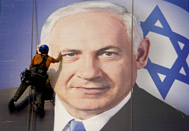 FILE - In this Thursday, Jan. 17, 2013 file photograph, a worker hangs a huge poster with an image of Israel's Prime Minister Benjamin Netanyahu overlooking the Ayalon freeway in Tel Aviv, Israel. After a lackluster three-month campaign, there seems to be little doubt that Prime Minister Benjamin Netanyahu is on his way to re-election. But the makeup of Netanyahu�s next government remains a matter of great uncertainty. (AP Photo/Ariel Schalit, File)
