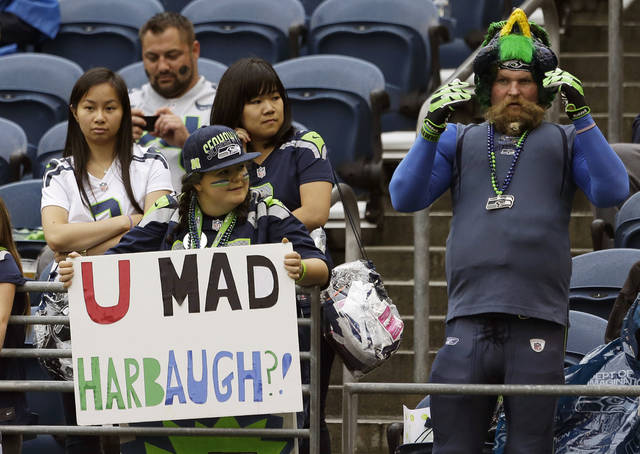 "Seattle Seahawks fans hold a sign that reads ""U Mad Harbaugh?"" in reference to San Francisco 49ers head coach Jim Harbaugh and Seattle Seahawks' Richard Sherman's famous ""You mad bro?"" quote before the start of NFL football game between the Seattle Seahawks and the San Francisco 49ers, Sunday, Sept. 15, 2013, in Seattle. (AP Photo/Elaine Thompson)"