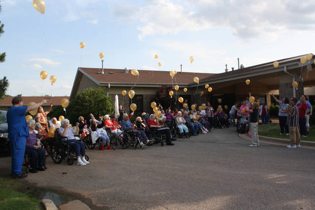 Residents of Grace Living Center - Brookwood release pen-pal balloons during National Nursing Home Week. Addresses of residents seeking pen pals were attached to some balloons.