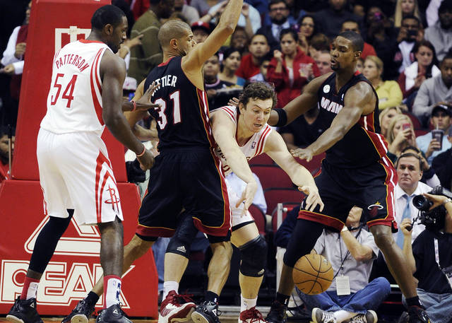 Houston Rockets' Omer Asik, second from right, chases a loose ball with Patrick Patterson (54) and Miami Heat's Shane Battier (31) and Chris Bosh, right, in the first half of an NBA basketball game, Monday, Nov. 12, 2012, in Houston. (AP Photo/Pat Sullivan)