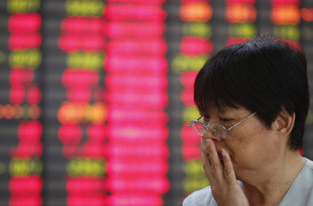 An investor looks at the stock price monitor at a private securities company Friday Sept. 21, 2012 in Shanghai, China. China's benchmark Shanghai Composite Index added 0.1 percent to 2,027.03 as Asian stock markets rebounded Friday, led by oil and technology shares, despite uncertainty about the fragile global economy. (AP Photo)